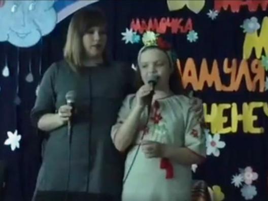 Юля співає зі своєю донечкою на сцені в актовому залі школи №2.