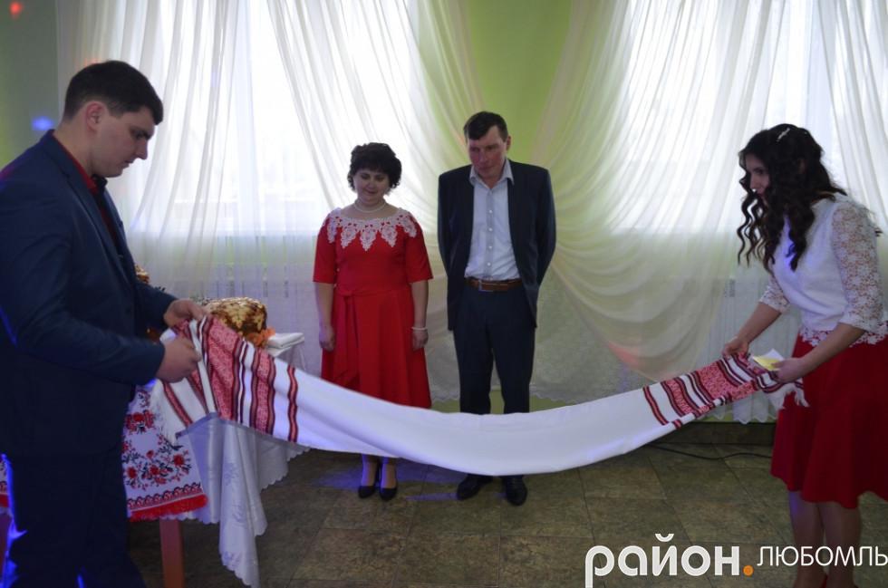 Діти розстелили весільний рушник своїм батькам.