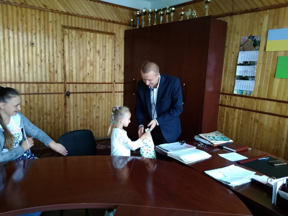 Міський голова Роман Ющук вручає подарунки доньці загиблого героя Сергія Кушніра Діані.