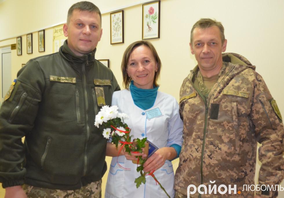 Олександр Лисенко і Юрій Ковальчук вручають нагороду волонтерціЛарисіШалаєвійна її робочому місці.