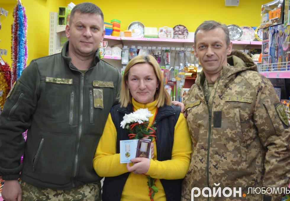 Олександр Лисенко і Юрій Ковальчук вручають нагороду волонтерці Каті Мокренко на її робочому місці.